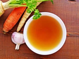 Clear bone broth in a white bowl and vegetables on wooden table top view.