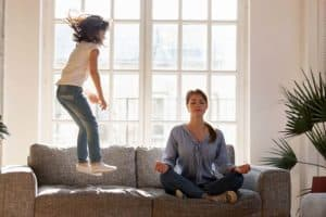 Young mom sit on couch at home meditating in lotus position, small daughter have fun jumping near, concentrated calm mother practice yoga relax on sofa ignore playful kid. Stress free concept.