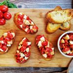 Caprese Bruschetta on a wooden cutting board with various ingredients spread around on a grey counter top.