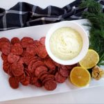 Beet crackers arranged on a plate with white bean dip (in a bowl), lemon, garlic and dill as a garnish. The white plate is on top of a navy blue checkered cloth napkin against a white background.