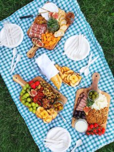 Charcuterie boards on a blue plaid picnic blanket with a grass background. Around the three boards are plates with compostable cutlery, and a plate that has a baguette and apple crisps on it.