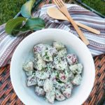 A creamy potato salad garnished with herbs on a wicker tray with a cloth napkin and wooden utensils on a grass background.