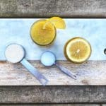 Photo of lemon sugar scrub on a marble slab on a picnic table background. Lemons and measuring spoons with sugar can also be seen.