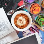 """A top-down view of """"Carrot Cake Oatmeal"""" in a white bowl against a messy desk background. On the desk are various papers, textbooks, an iPad, an open laptop and a spoon."""