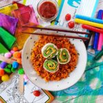 """A top-down shot of """"Cheesy Green Eggs And Ham Roll-Ups"""" on a white plate with mahogany-coloured chopsticks on a messy wooden desktop background. On the desk are various papers, markers, stencils and a small mason jar of sauce."""