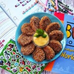 Hidden broccoli chicken nuggets on a blue plate arranged around a yellow sauce garnished with basil leaves. The background is a white wooden table with children's coloring books scattered around the plate.