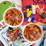 Two bowls of pasta garnished with cheese and herbs on a brick background with children's books scattered around it and two metal forks.