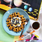 """A top-down shot of """"Sweet Potato Waffles"""" on a blue plate with a fork and a small bowl of maple syrup off to the side against a messy desk background. On the desk are various coloured papers, Sharpie markers and an open book about the solar system displaying the planets and some informational text."""