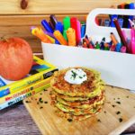 """""""Zucchini Fritters"""" garnished with herbs on a wooden cutting board. Surrounding the dish are some decorative books with a red apple on top and a white caddy-style container with various stationery inside of it (pencils, crayons, markets and etcetera)."""