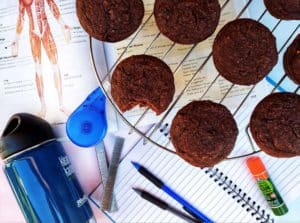 A top-down shot of Chocolate Zucchini Protein Muffins on a circular cooling rack on top of a table with stationery and school supplies on it.