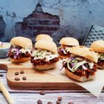 BBQ Coffee Pulled Jackfruit Sliders on parchment paper on a wooden cutting board with coffee beans, a wooden spoon with coffee beans in it, a bowl of coleslaw and a cheese grater on it's side. They are situated on a wooden table surface and have an exposed brick and concrete design on the background wall.