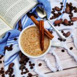 A top-down shot of Mushroom Latte on a fancy cloth with coffee and cacao beans around it. They are on a wooden plank-style table, along with an open book.