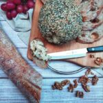 A top-down shot of Everything Bagel Cheeze Ball on a wooden cutting board with a metal handle with slices of baguette and a small serrated knife. It's on a plank wood-style counter top with the rest of the baguette, walnuts, grapes and a beige cloth as decorations surrounding the cutting board.