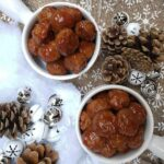 A top-down image of two servings of Honey Garlic Turkey Meatballs in soup bowls on a brown Christmas tablecloth with white snowflakes. Around it are silver and white ornaments and pine cones with fake cotton snow.