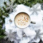 An overhead shot of a latte drink with fake snow, ornaments and evergreen branches as a decoration on a grey concrete-style countertop.