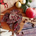 A top-down picture of Chocolate Pomegranate Bark on a cutting board with a whole pomegranate, Christmas ornaments and decorations around it on a dark brown plank wood table.