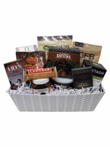 A white rectangular gift basket with black line chevron pattern. In the basket is a variety of chocolate bars and other chocolate-based products.