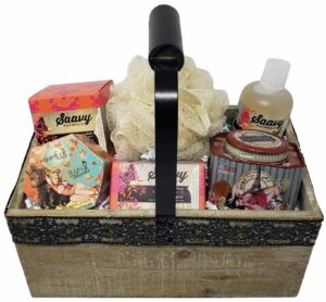 A rectangular wooden gift basket with a black metal handle with a black wooden grip. Inside it are various home spa products.