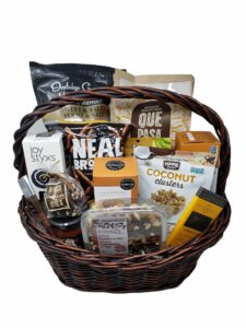 A brown wicker basket with a brown wicker handle with various snacks inside it, including mixed nuts, chocolate bars and salsa.