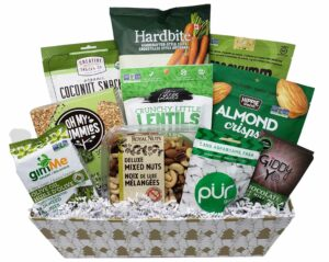 A white and gold Christmas tree rectangular gift basket with various vegan snacks inside, including mixed nuts, chewing gum, mint chocolate bars, dehydrated seaweed snacks and more. The products in the basket are mostly green and/or white, giving it that colour scheme overall.
