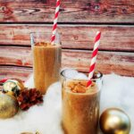 Two smoothie drinks with red and white striped paper straws on a brown wood panel backround. Around it (as decorations) are fake snow, various golden ornaments and decorative pinecones.