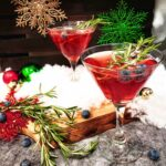 Two red mocktail drinks in cocktail glasses with blueberries and sprigs of rosemary as a garnish. One drink is on a cracked-concrete style countertop and the other is elevated on a wooden cutting board. Scattered around (as decorations) are red, green and gold Christmas ornaments, blueberries, fake snow and a large sprig of rosemary.