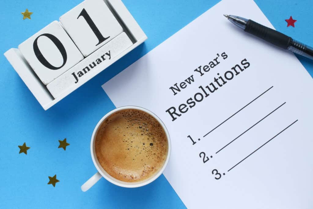 "A top-down image of a paper list titled ""New Year's Resolutions"" with a list of three lines to write your resolutions into. It is surrounded by a pen, a cup of black coffee, gold/red stars, and a white wooden date block set for January 1st. Everything is on a blue background."