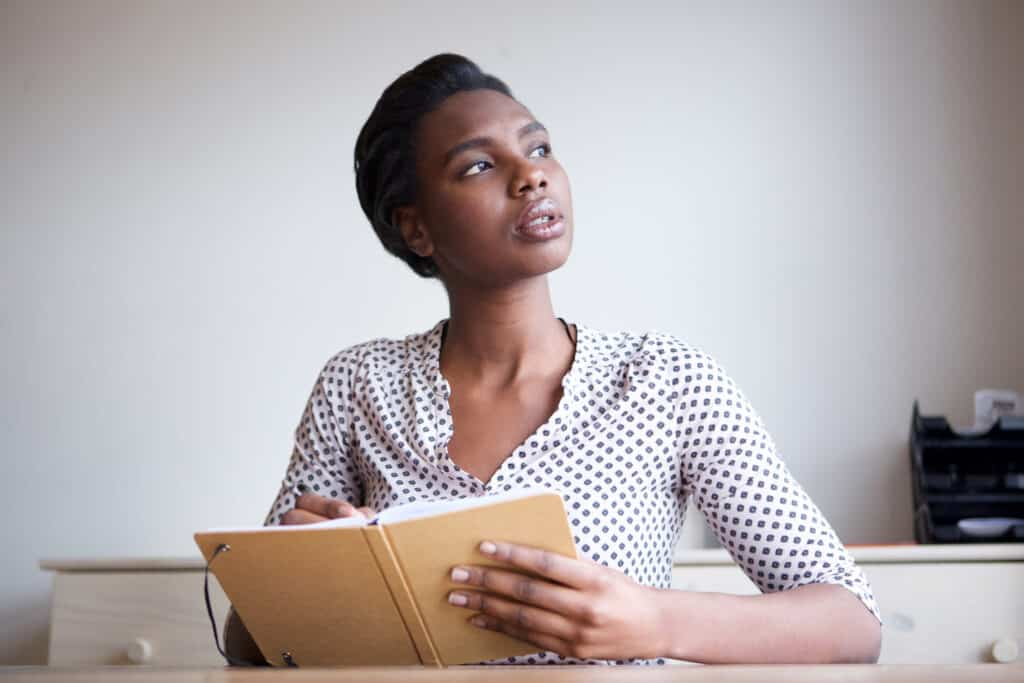 A portrait of a serious-looking young woman thinking and writing in journal.