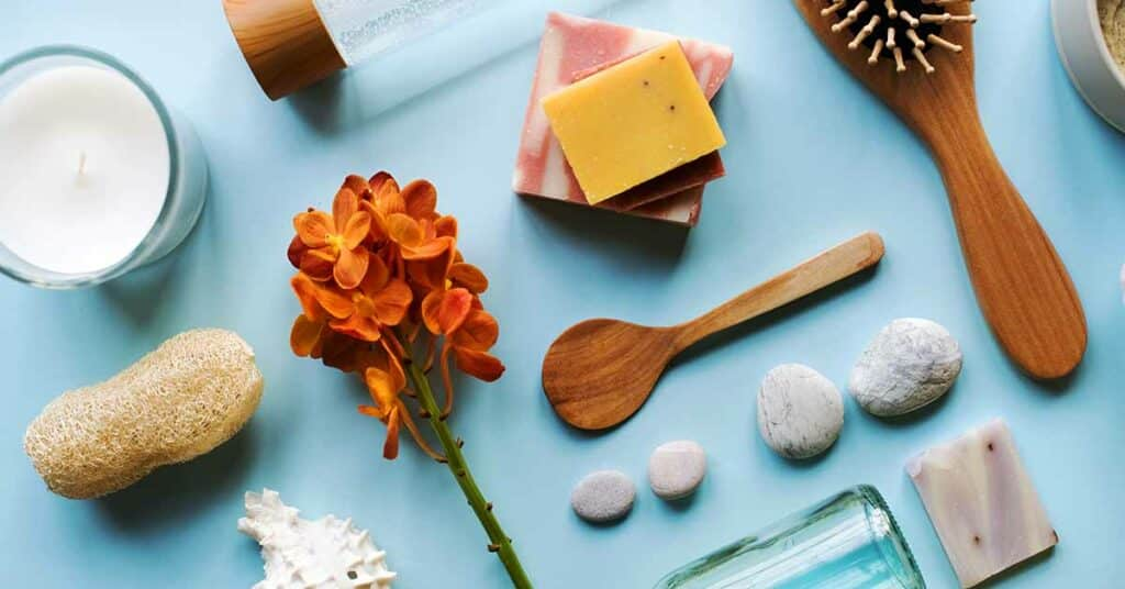 Skin care and aromatherapy objects laid out flat on a sky-blue countertop.