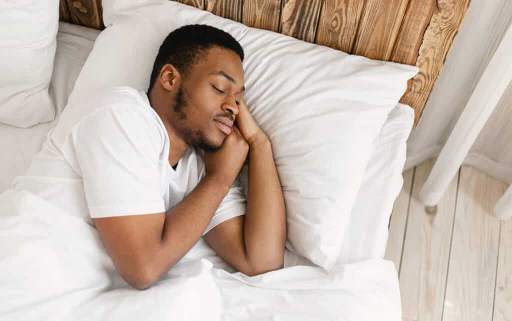 A man sleeping peacefully resting with eyes closed lying in a comfortable bed in his bedroom at home.