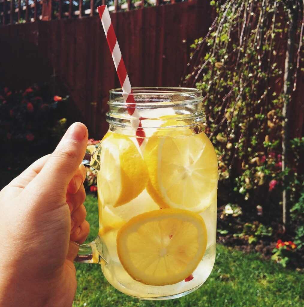 Lemon water held by a hand in a mason jar mug outside in the backyard garden. In the mug, there is a red and white pinstripe paper straw.