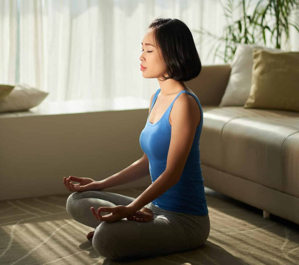 A woman meditating at home in the morning.
