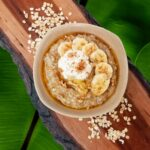 Oatmeal with bananas in it on a wooden cutting board with oats on it as aa decoration. It is in front of a banana leaf background.
