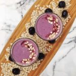 A pink smoothie with outs in it shown from a top-down view. The glasses are on a wooden cutting board with oats and cherries as decorations. The cutting board is on a marble background.