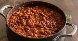 Organic vegetarian chili in iron pot served with rosemary on a distressed wood country table.