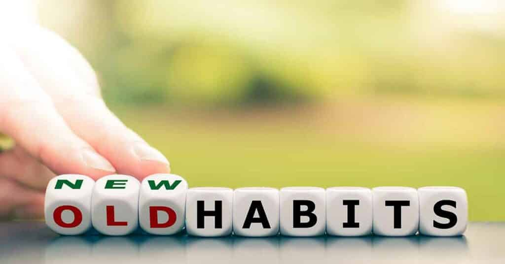 "Hand turns dice and changes the expression ""old habits"" to ""new habits."""