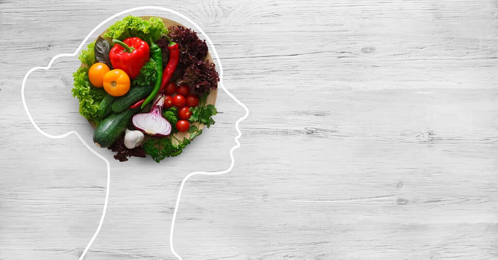 A graphic of fresh vegetables in a drawing of a woman's head symbolizing health nutrition.