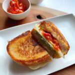 A grilled cheese sandwich on a plate and wooden cutting board with decorative bowls of cherry tomatoes and pesto.