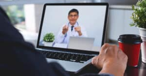 Doctor explaining to patient via laptop computer for telemedicine and medical online e-health consultation.