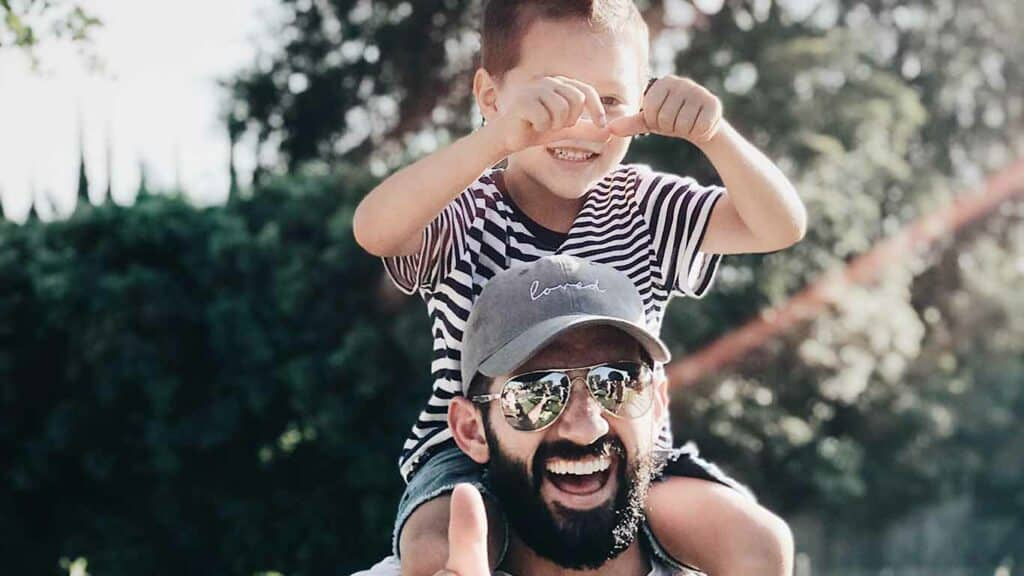 A father with a beard, sunglasses and a hat with his son on his shoulders. They both look happy with joyful expressions.